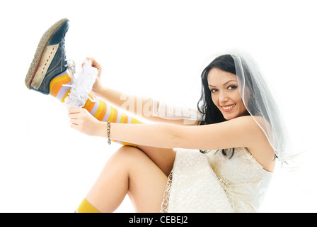 funny young bride wearing sporting shoes puts on a garter and smiles - Stock Photo