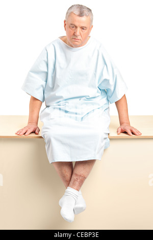 A worried senior patient sitting in a hospital after hearing a bad diagnose isolated on white background - Stock Photo