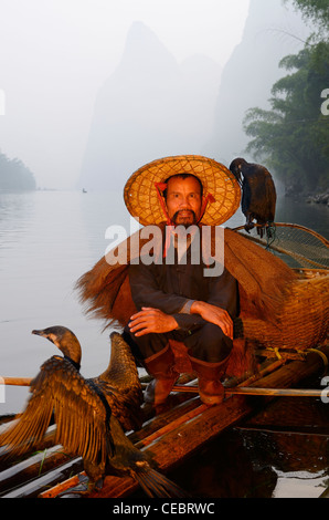 Cormorant fisherman resting with birds on a bamboo raft on the Li river with Karst mountain peaks Huangbutan China - Stock Photo