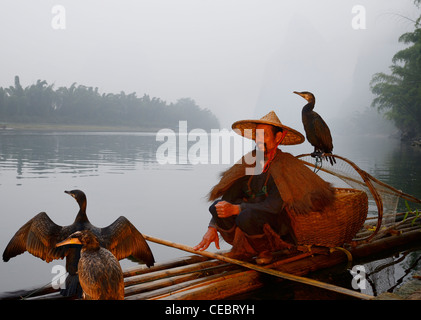 Cormorant fisherman with birds on a bamboo raft on the Li river with Karst mountain peaks Xingpingzhen Yangshuo, - Stock Photo