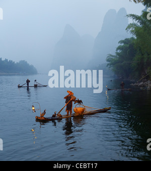 Cormorant fishermen in mist at dawn on the Li river with Karst mountain peaks near Xingping China - Stock Photo