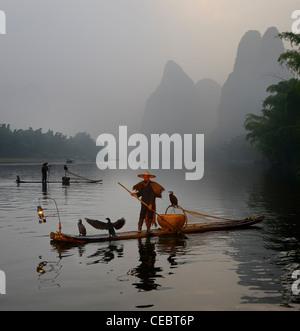 Cormorant fishermen paddling bamboo rafts at dawn on the Li river with Karst mountain peaks Xingpingzhen Yangshuo, - Stock Photo