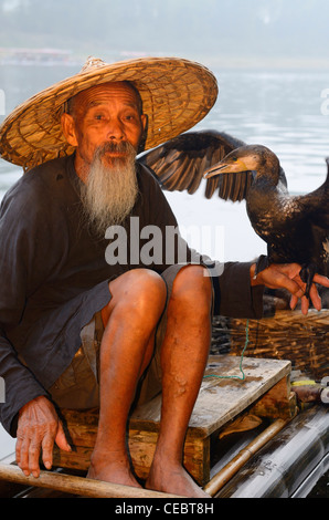 Cormorant fisherman holding bird on a bamboo raft on the Li river Huangbutan China - Stock Photo