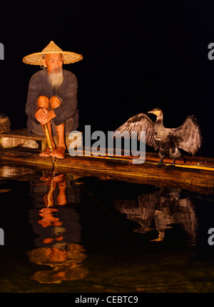 Cormorant fisherman and bird with spread wings reflected in the Li river at night from a bamboo raft Xingpingzhen - Stock Photo