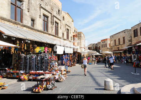 Shoppers walking around the shops in Rhodes Old Town - Stock Photo