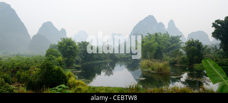 Panorama of receeding Karst limestone peaks in haze on the Yulong river Yangshuo Peoples Republic of China - Stock Photo