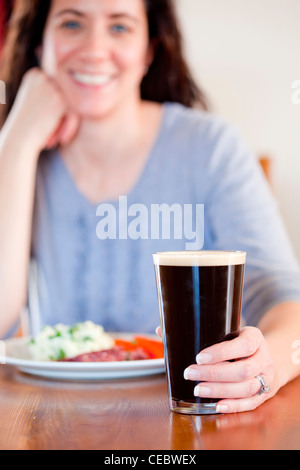 Young woman holding a pint with lunch at a pub - Stock Photo