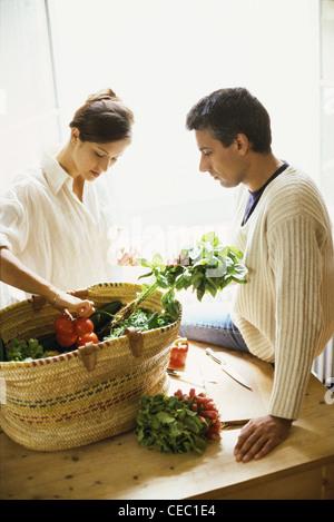 Couple emptying basket of fresh produce - Stock Photo