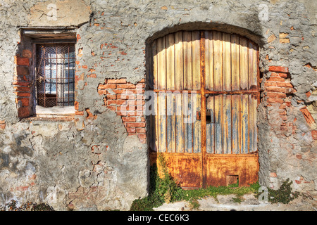 Old brick wall with metal rusty gate and small window in town of La Morra, Northern Italy. - Stock Photo
