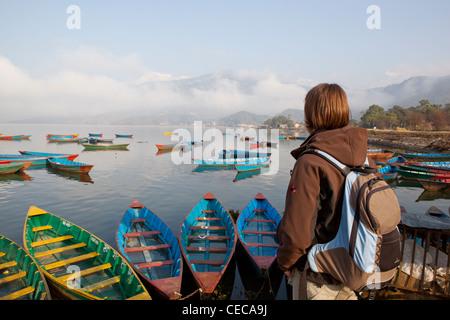 Woman overlooking colourful boats on Phewa Lake Pokhara Nepal Asia - Stock Photo