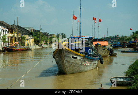 In Hoi An, a historic Vietnamese trading port, wooden fishing boats are anchored in the Thu Bon river - Stock Photo