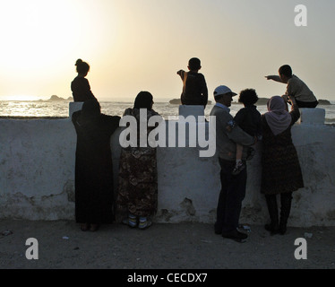 Children point out to sea as a Moroccan family watches the sunset in Essaouira, Morocco - Stock Photo