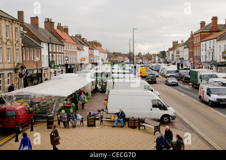 Busy bustling scenic town (Northallerton High Street) on market day (stalls, people shopping, vehicles on road, - Stock Photo
