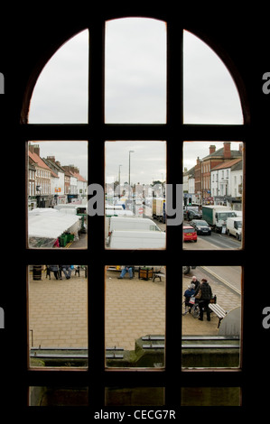 View through window of busy bustling town (Northallerton High Street) on market day (stalls, people shopping, road) - Stock Photo