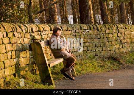 Man (walker) seated on wooden bench seat, resting & relaxing in quiet sunny scenic spot (by stone wall & trees) - Stock Photo
