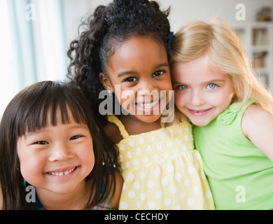Smiling girls hugging each other - Stock Photo