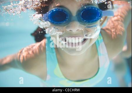 Hispanic girl swimming under water - Stock Photo