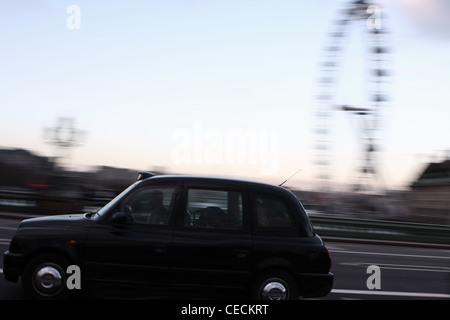 a taxi traveling over Westminster bridge and passed County Hall and The London eye in London - Stock Photo