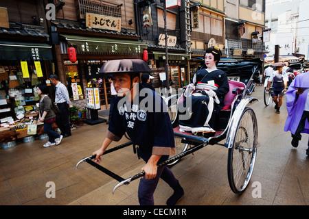 Geisha in Rickshaw on busy street. Japan,Tokyo - Stock Photo