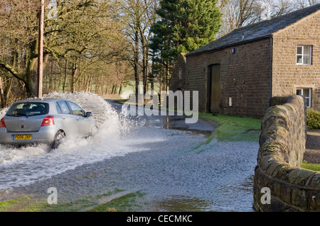 Flooding - silver car (Toyota) driving & splashing through deep flood water on flooded rural road after torrential - Stock Photo