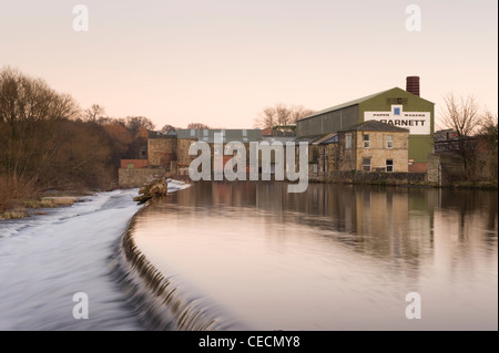 River Wharfe water gently flowing & cascading over weir under sunset sky, historic Garnett's paper mill beyond  - Stock Photo