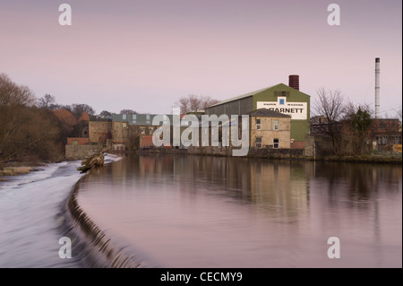 Flowing water of River Wharfe cascading over weir under pink sunset sky, historic Garnett's paper mill beyond - - Stock Photo