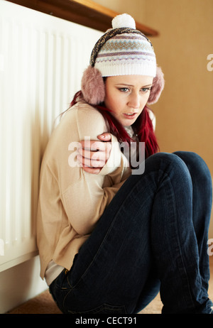 Cold girl next to radiator - Stock Photo
