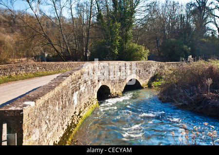 An arched Cotswoldstone bridge over a small river the By Brook in the village of Slaughterford, Wiltshire, England, - Stock Photo