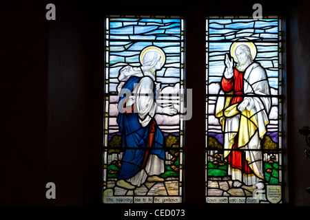 Stained glass window depicting Mary Magdalene and Jesus Christ in English village church in Biddestone, Wiltshire, - Stock Photo
