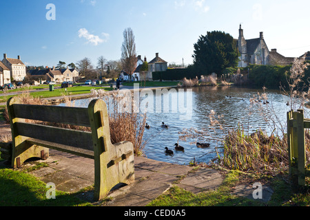 A typical English village duck pond on the green in Biddestone, Wiltshire, England, UK - Stock Photo