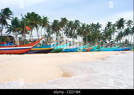 Traditional sri lankan fishing boats on ocean beach - Stock Photo