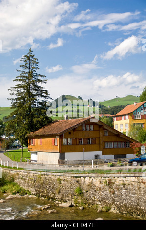 Vertical view of typical Swiss wooden chalet building next to a stream in the Swiss countryside on a sunny day. - Stock Photo