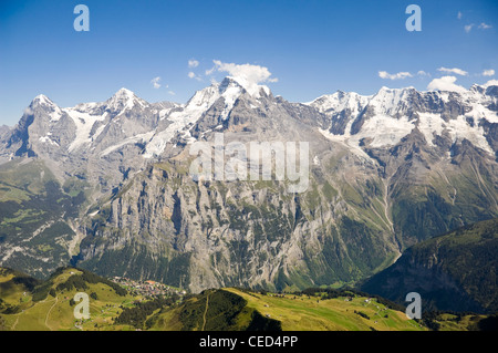 Horizontal wide angle view of the Jungfrau, Mönch and Eiger in the Bernese Alps on a bright clear day. - Stock Photo