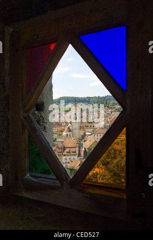 Vertical wide angle view of Schaffhausen through an old stained glass window inside the Munot, on a bright sunny - Stock Photo