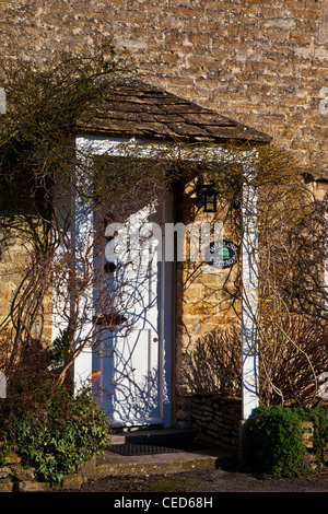 Gabled porch and white fornt door of a typical Cotswold stone cottage in winter. - Stock Photo