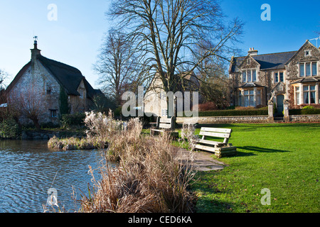 Houses around a typical English village duck pond on the green in Biddestone, Wiltshire, England, UK - Stock Photo