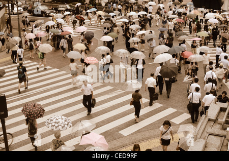Pedestrians cross at Shibuya Crossing in Tokyo, Japan, the world's busiest crossing. - Stock Photo