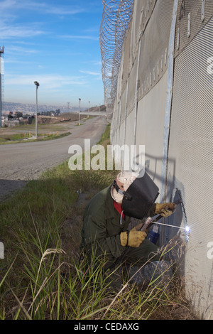 Worker Patches Hole Cut in U.S.-Mexico Border Fence - Stock Photo