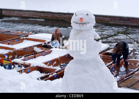 A snowman in the foreground as students clear the snow off the punts on the river Cam, Cambridge, England. - Stock Photo