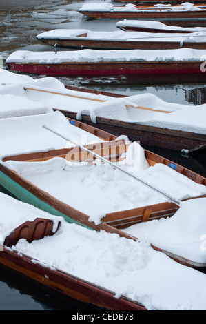 Punts covered with snow in winter. Cambridge, England. - Stock Photo