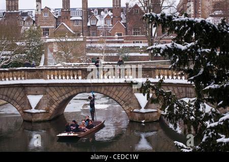 Punting under Kitchen bridge in winter snow. Cambridge. England. - Stock Photo