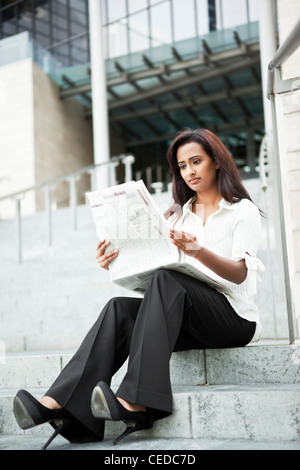 Indian businesswoman reading newspaper outdoors