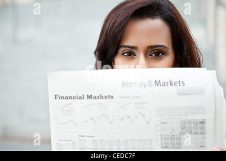 Indian woman reading newspaper - Stock Photo