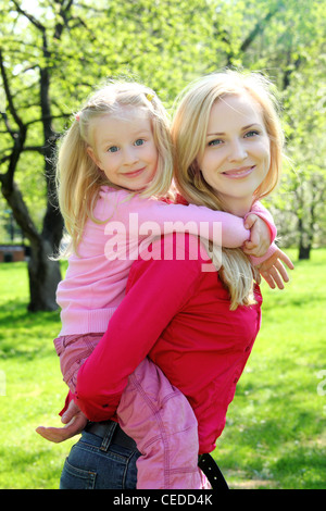 daughter sits at mother on back in spring park - Stock Photo
