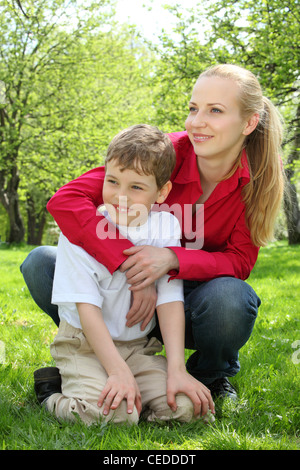 Mother embraces behind  son sitting on laps on grass in park in spring - Stock Photo