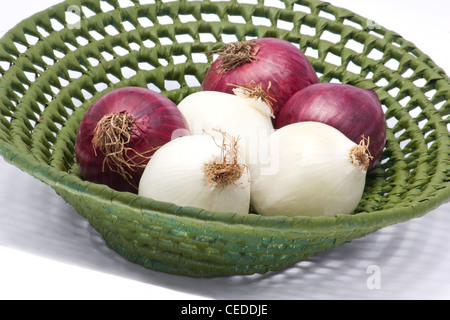 White and red onions in a basket on white background - Stock Photo