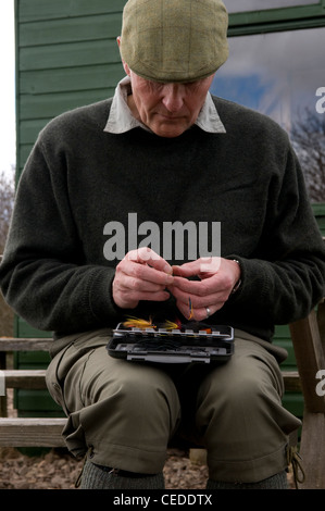 Angler sitting, choosing a fly to fly fish on the River Oykel, Sutherland, Scotland, UK - Stock Photo