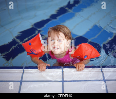 A Young Girl In Arm Bands And A Boy Swimming In A Pool At