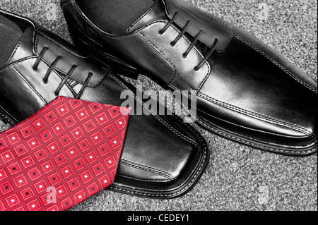 A red necktie on a new pair of black leather dress shoes - Stock Photo