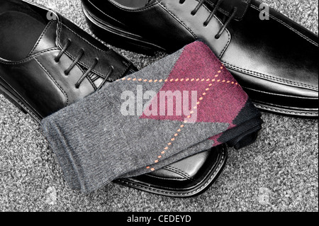 A pair of black leather dress shoes with argyle socks - Stock Photo